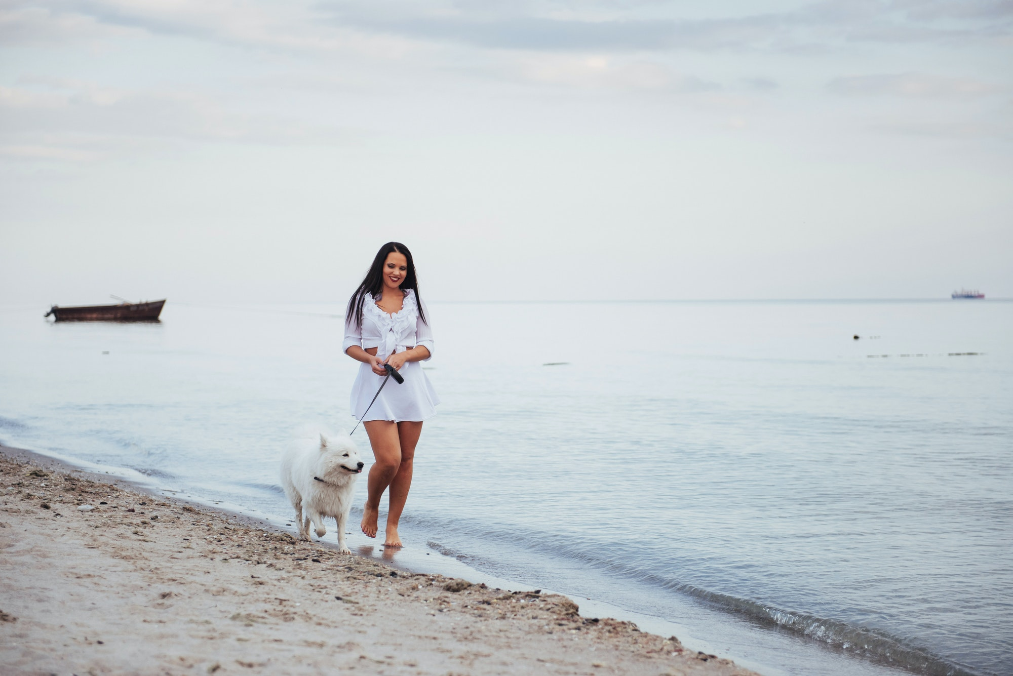 Beautiful brunette woman on the beach with a dog walking